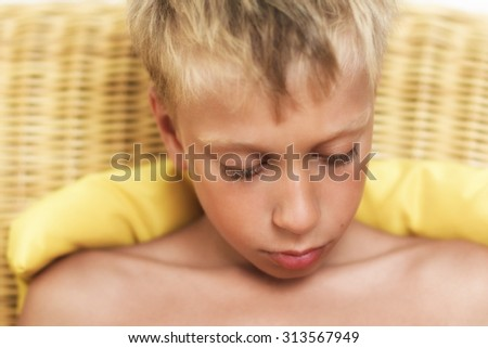 Close up portrait of beautiful funny little child sitting on wicker sofa looking very sad and frustrated. Vintage effect, soft-focus.  - stock photo