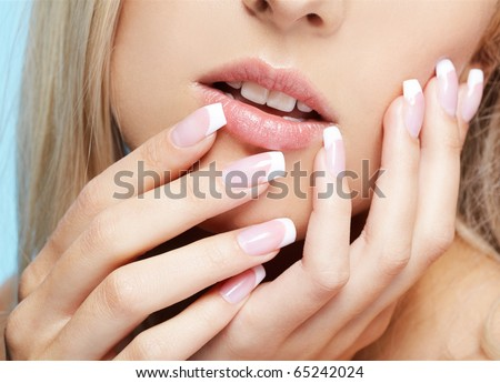 close-up portrait of beautiful girl's lower part of face and manicured fingers - stock photo
