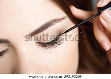Close-up portrait of beautiful girl touching black eyeliner to her eyelid. Her eyes are closed - stock photo