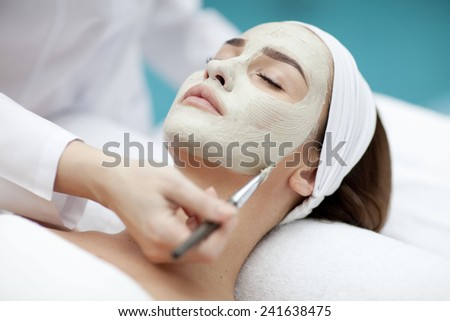 Close-up portrait of beautiful girl with a towel on her head applying facial mask - stock photo