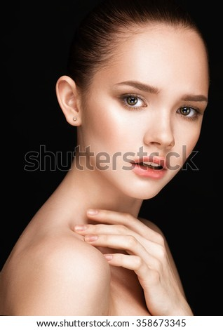 Close-up portrait of beautiful girl with clear healthy skin. Looking at the camera. Touching neck. Beauty studio shot over black background. - stock photo