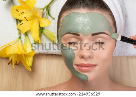 Close-up portrait of beautiful girl with closed eyes  with a towel on her head applying facial clay mask and beauty treatments lying on a table in spa near yellow flower - stock photo