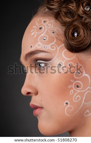 Close up portrait of beautiful girl with curly hair style, spiral face and body art and stars