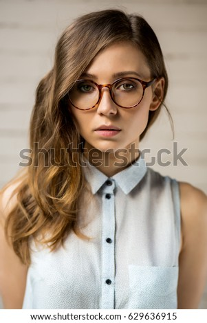 Close up portrait of beautiful hipster lady in trendy glasses looking to the camera. Gorgeous pretty sexy girl in eyeglasses. White urban wall background. Business, active, freedom lifestyle concept.