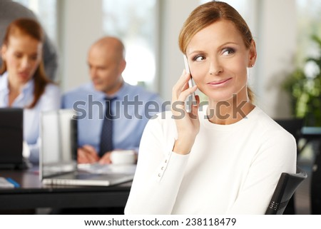 Close-up portrait of beautiful mature business woman sitting at meeting while using her mobile. - stock photo