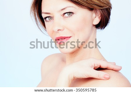 Close up portrait of beautiful middle aged woman with short brown hair, red lips and fresh makeup standing with hand on her shoulder over blue background - beauty concept - stock photo