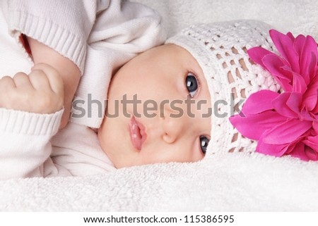 Close-up portrait of beautiful newborn baby girl in knitting hat with bright pink flower, studio shot - stock photo