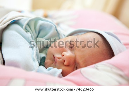Close-up portrait of beautiful one week old baby boy asleep - stock photo