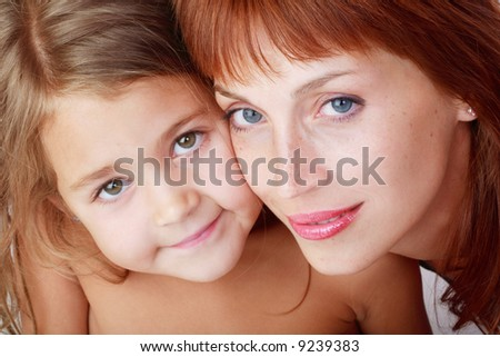 Close-up portrait of beautiful red-haired mother and cute daughter