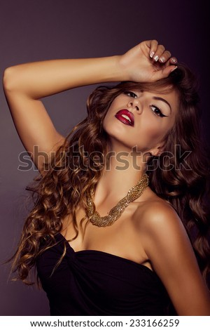 Close up portrait of beautiful sexy stylish young woman with perfect clean skin in studio. Model shooting. High fashion look. Gold jewelry. Fashion makeup and hairstyle. Long curly hair
