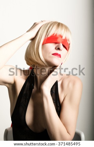 Close up portrait of beautiful sexy young blonde woman  with a bandage on his eyes, puts her hand to her hair - stock photo