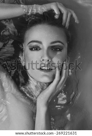 Close up portrait of beautiful sexy young woman lying in the bathtub. With gorgeous make-up, gently touching her pretty face by hands with nail polish. Black and white image.  - stock photo