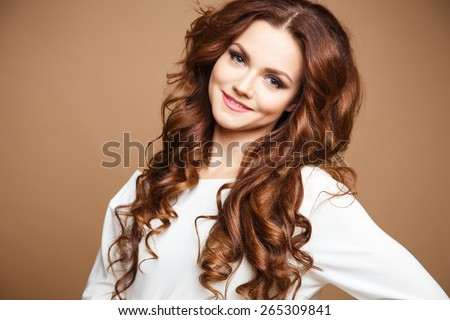Close-up portrait of beautiful sexy young woman with long brown hair over brown background - stock photo