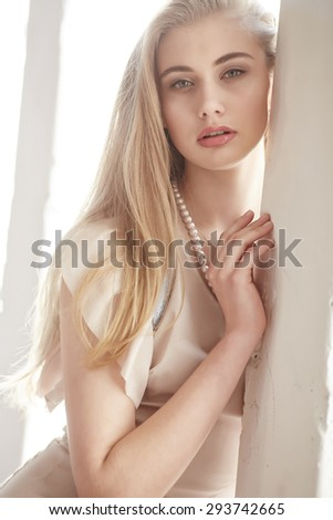 Close up portrait of beautiful slim female with long blond hair and red lips. - stock photo