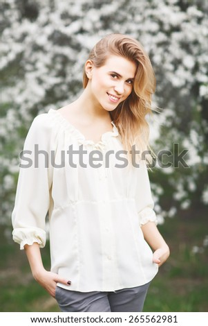 Close up portrait of beautiful smiling  girl in blossom garden on a spring day - stock photo