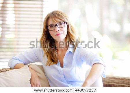 Close-up portrait of beautiful smiling woman sitting on sofa in luxury living room.