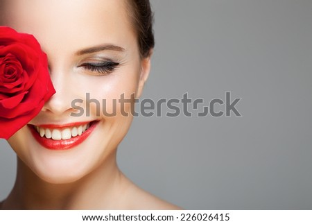 Close-up portrait of beautiful smiling woman with red rose. Make-up face. - stock photo
