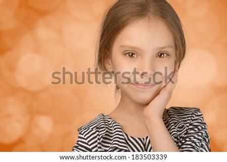 Close-up portrait of beautiful smiling young girl, on orange background. - stock photo