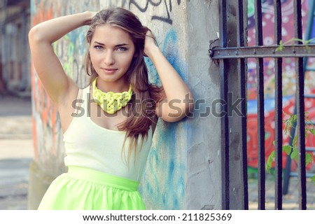 close up portrait of beautiful stylish fashion woman fair hair blond girl having fun gently smiling and looking at camera on graffiti wall city urban summer or spring outdoors copy space background - stock photo