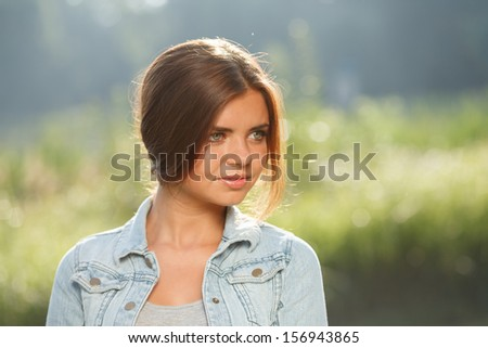 close-up portrait of beautiful teenage girl outdoors in jeans wear looking away