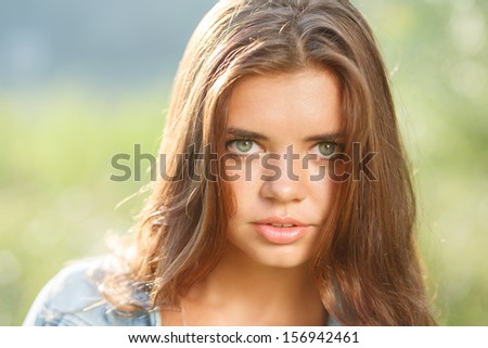 close-up portrait of beautiful teenage girl outdoors looking at camera