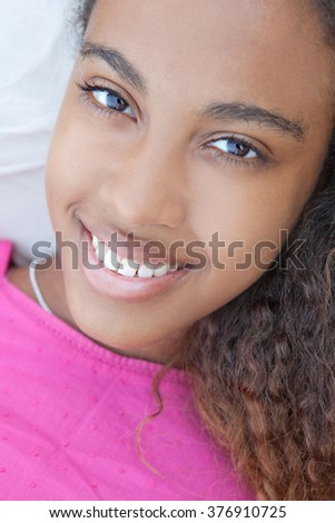 Close up portrait of beautiful teenager black girl smiling looking at the camera, laying relaxing on a summer beach holiday, outdoors. African american adolescent lifestyle, joyful face expression. - stock photo