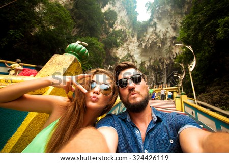 Close-up portrait of beautiful travel couple,wear casual hipster outfit,make selfie of their trip,positive mood,happy couple,couple wear sunglasses,shows tongue,crazy self portrait,emotional people   - stock photo