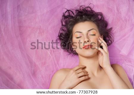 Close-up portrait of beautiful woman lying on pink fabric - stock photo