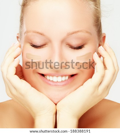Close-up portrait of beautiful woman model with clean skin, foundation cream on cheeks - stock photo