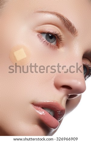 Close-up portrait of beautiful woman's purity face with natural make-up. Cute model with clean shiny skin. Beautiful young woman with clear-up patches or plaster on her skin. Skin care concept - stock photo