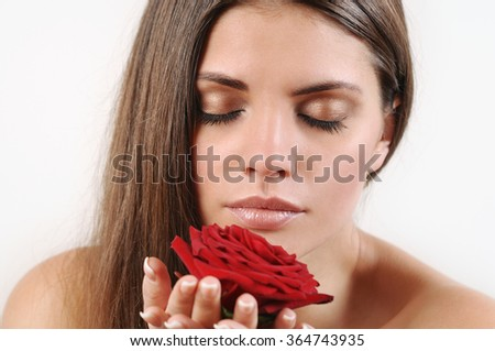 Close up portrait of  beautiful woman smelling red rose on white background. Pure skin and strong healthy bright hair. Spa beauty concept - stock photo