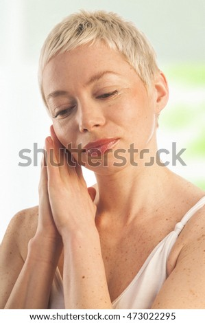 Close up portrait of beautiful woman touching her face, skin-care concept