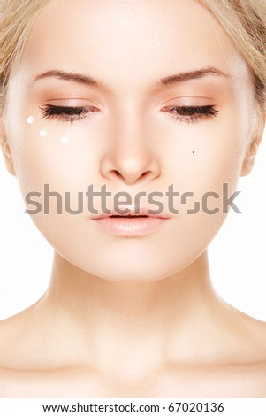 Close-up portrait of beautiful woman which applying cream near eyes. Cosmetology & cosmetic.