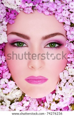 Close-up portrait of beautiful woman with bright makeup and flowers around her face - stock photo