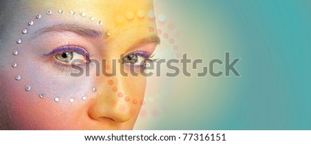 Close-up portrait of beautiful woman with bright makeup, paste, crystals and copyspace - stock photo