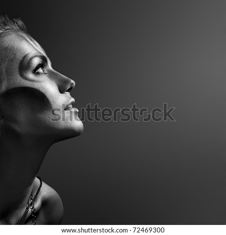 close-up portrait of beautiful woman with silver bodyart - bw image