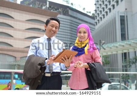 Close-up portrait of beautiful young Asian businesswomen and businessman discuss together