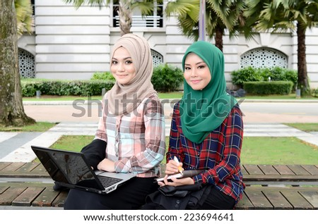 Close-up portrait of beautiful young Asian businesswomen discuss together - stock photo
