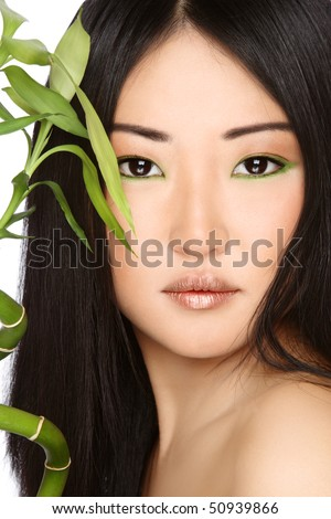 Close-up portrait of beautiful young asian girl with green bamboo - stock photo
