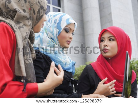 Close-up portrait of beautiful young Asian student discussing, focusing at the girl wearing red scarf - stock photo