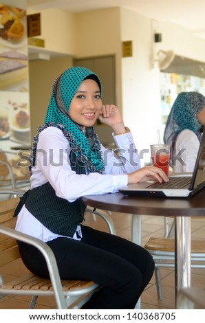 Close-up portrait of beautiful young Asian student smile at cafe - stock photo