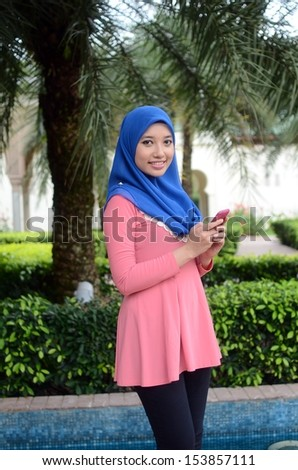 Close-up portrait of beautiful young Asian student with mobile phone - stock photo