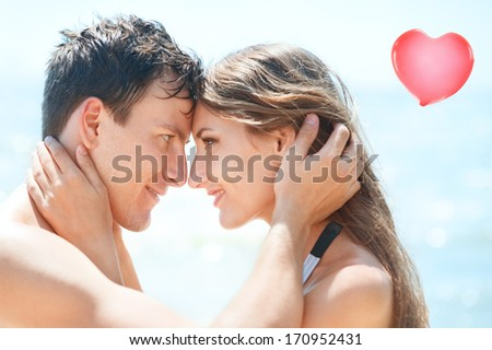 Close-up portrait of beautiful young couple. They are  smiling and looking at each other. - stock photo
