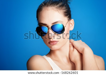 Close-up portrait of beautiful young girl in blue sunglasses on dark blue background - stock photo