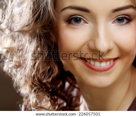 Close up portrait of beautiful young happy smiling curly woman