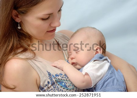 close-up portrait of beautiful young mother tenderly keeping her baby on light blue background - stock photo