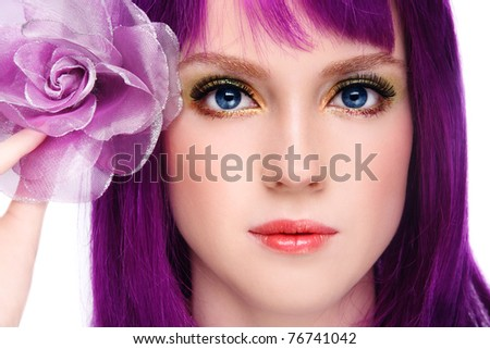 Close-up portrait of beautiful young smiling girl with fancy bright make-up and violet wig - stock photo