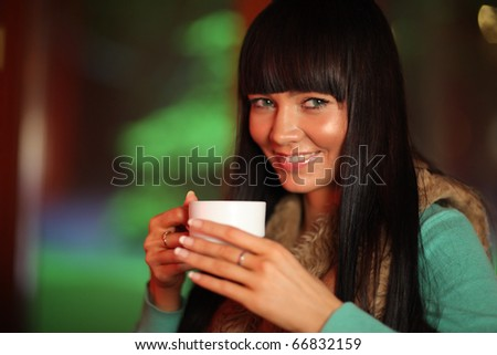 Close-up portrait of beautiful young woman holding cup of tea or coffee. Shallow DOF - stock photo