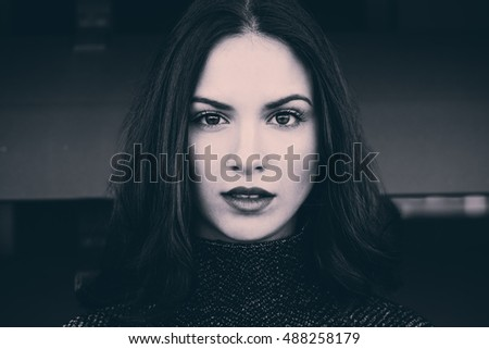 Close-up portrait of beautiful young woman looking at camera with intense look. Black and white and tinted photograph.