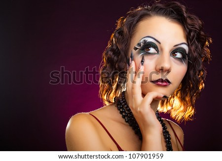 Close-up portrait of beautiful young  woman model with retro glamour makeup and extravagant manicure on dark background - stock photo